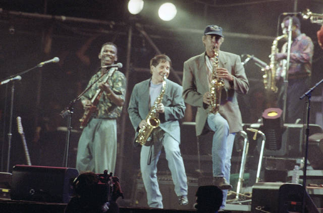 In this Aug. 16, 1991, file photo, Paul Simon, center, plays a finale with lead guitarist Ray Phiri, left, and actor-comedian Chevy Chase on the saxophone in New York's Central Park. Ray Phiri, a South African jazz musician who founded the band Stimela and performed on Paul Simon's Graceland tour, died of cancer on Wednesday at the age of 70.