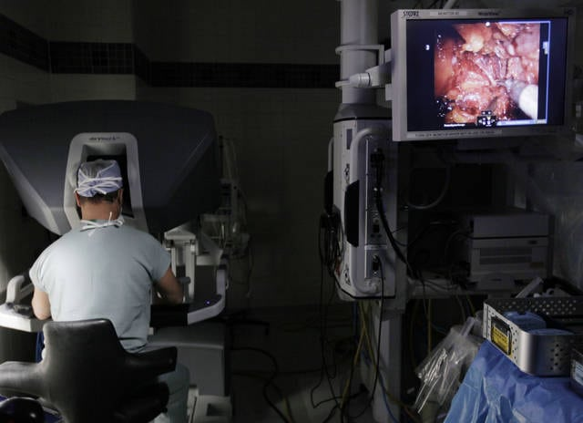 In this Oct. 13, 2009, file photo, a surgeon performs a robotic prostatectomy on a patient in Chicago. According to a report released on Wednesday, July 12, 2017, long-term results comparing different approaches for men with cancers confined to the prostate show that after 20 years, death rates were similar for those who had immediate surgery as for those initially assigned to monitoring.