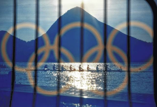 In this Aug. 7, 2016, file photo, rowers are seen through a screen decorated with the Olympic rings as they practice at the rowing venue in Lagoa at the 2016 Summer Olympics in Rio de Janeiro, Brazil. The Olympic Channel, a new Olympic-themed television network, makes its debut on Saturday.
