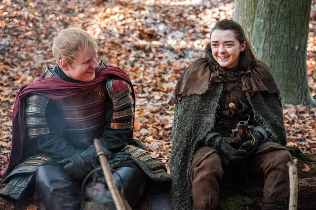 "This image released by HBO shows Ed Sheeran, left, and Maisie Williams in a scene from ""Game of Thrones."" Sheeran appeared as a Lannister soldier leading a group in song in the season premiere of the hit HBO fantasy drama, which debuted on the premium cable channel Sunday night."