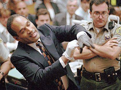 In this June 15, 1995, file photo, O.J. Simpson, left, grimaces as he tries on one of the leather gloves prosecutors say he wore the night his ex-wife Nicole Brown Simpson and Ron Goldman were murdered in a Los Angeles courtroom. Simpson, the former football star, TV pitchman and now Nevada prison inmate, will have a lot going for him when he appears before state parole board members Thursday seeking his release after more than eight years for an ill-fated bid to retrieve sports memorabilia.