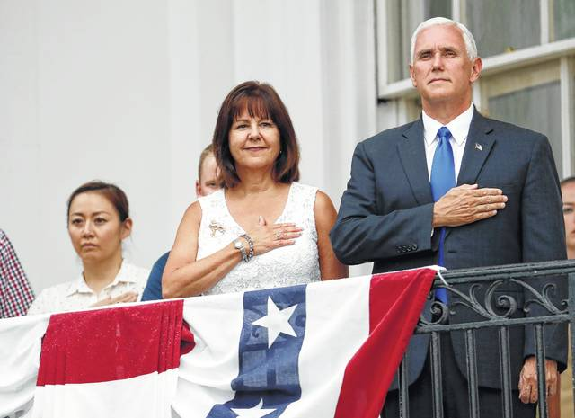 Vice President Mike Pence, right, and his wife, Karen Pence, second from right, stand during the national anthem on the Truman Balcony at the Fourth of July picnic for military families on the South Lawn of the White House on Tuesday in Washington.