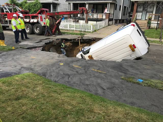 A tow truck pulls a Cleveland Division of Water van from a sinkhole that opened up beneath it in Cleveland on Thursday.