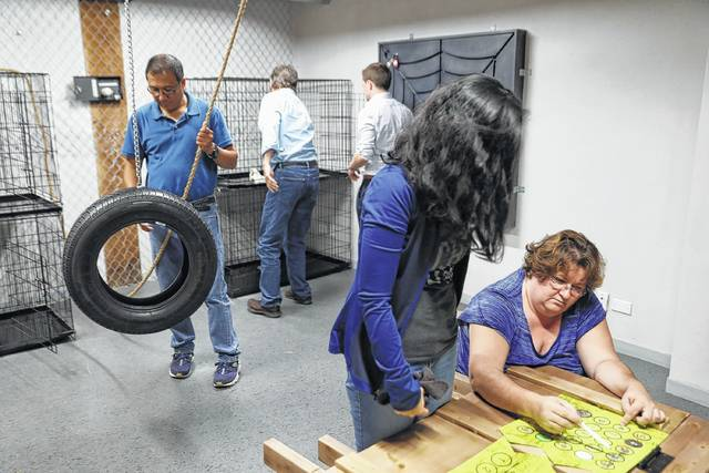 """United Airlines employees, including Lizzie Cristobal, standing right, and Rhonda Crenshaw, seated right, take part in a corporate team building exercise, working together to free themselves from an """"escape room"""" at PanIQ Escape Room Chicago on June 29."""