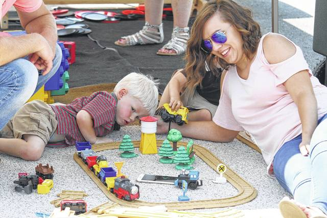 Colin Knippen, 2, of Ottoville, takes a break from the festival activities and sun to find shade and play with trains with family friend Jessica Wurst on Sunday afternoon.