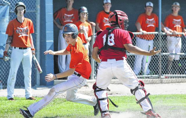 Elida's Justin Moore evades Wapakoneta catcher Bubba Smith to score a run in the third inning of the ACME District 5 Sectional game Sunday.