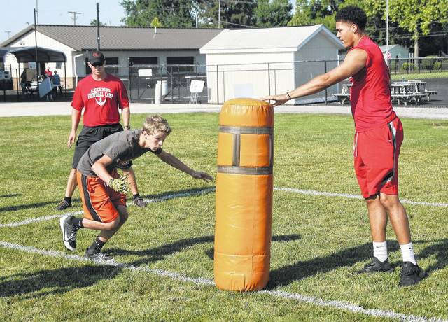 Lima Senior's Keaton Upshaw holds up the tackle dummy as part of a tackling drill during Saturday's U.S. Plastics District 8 Fellowship of Christian Athletes youth football camp at Elida High School.