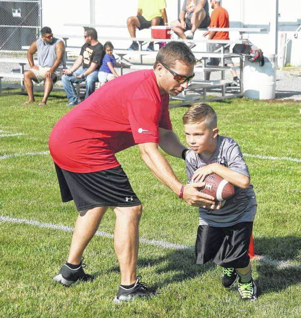 Spencerville Athletic Director John Zerbe hands off to Brody Sherrick in one of the 20 drills during Saturday's U.S. Plastics District 8 Fellowship of Christian Athletes youth football camp at Elida High School held as part a Legends of Northwest Ohio Weekend. See more photos at LimaScores.com.