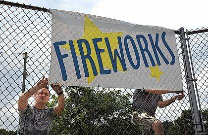 Chairman Dan McCormick, left, and co-chairman Jeff Ramey tie a fireworks banner to a fence at Faurot Park on Monday in preparation for Tuesday's Star Spangled Spectacular. Fireworks start at 10 p.m.