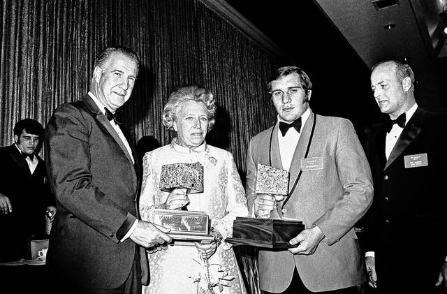 FILE – In this Jan. 22, 1971, file photo, Vice President Spiro T. Agnew, left, presents the first Lombardi Award to Ohio State defensive tackle Jim Stillwagon, second from right, in Houston. Former Ohio State linebacker Chris Spielman filed a federal lawsuit Friday, July 14, 2017, against the university on behalf of several of the school's most famous former student-athletes including Stillwagon, running back Archie Griffin, safety Mike Doss and others, over a marketing program the ex-athletes say used their photos without permission and robbed them of compensation.