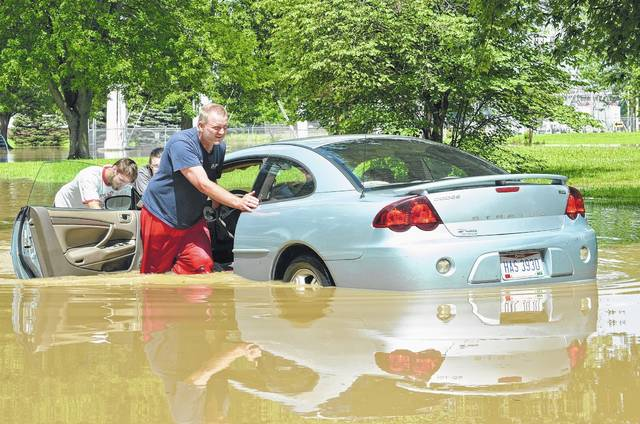 Tyler Straley, from left, Ally Mahlmeister and Don Hovest push Mahlmeister's car up Third Street in Ottawa at noon Friday. Mahlmeister was helped by her father, Hovest, and her boyfriend, Straley. See more photos of flooding on 5A.
