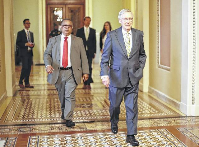 FILE - In this July 13, 2017 file photo, Senate Majority Leader Mitch McConnell of Ky. walks to his office on Capitol Hill in Washington. Republicans' latest health care plan would create winners and losers among Americans up and down the income ladder, and across age groups.
