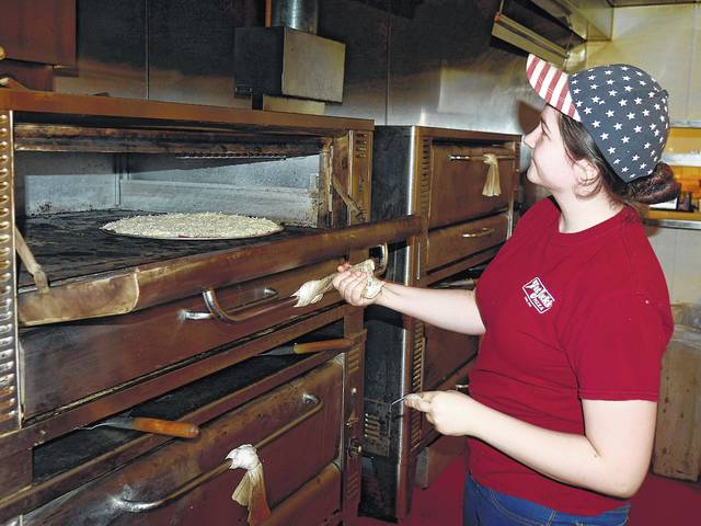 Adaleigh Staley puts a pizza in the oven at Fat Jack's on Spencerville Road.
