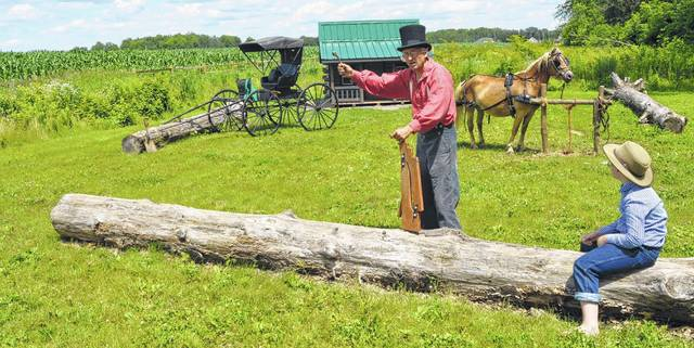 Mark Mohr, a historic re-enactor dressed in garb from the 1800s, holds up a wooden jack that people used to use when their horse and buggy broke down. Looking on is Isaac Richard, who is also dressed in traditional clothing from the 19th century.