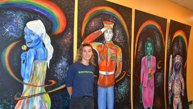 Lima Senior High School student Cora Bicknell stands near the series of murals she painted for the Mizpah Community Center in Lima. Bicknell said the paintings, which depict people in various professions, are meant to inspire youth to achieve their dreams.