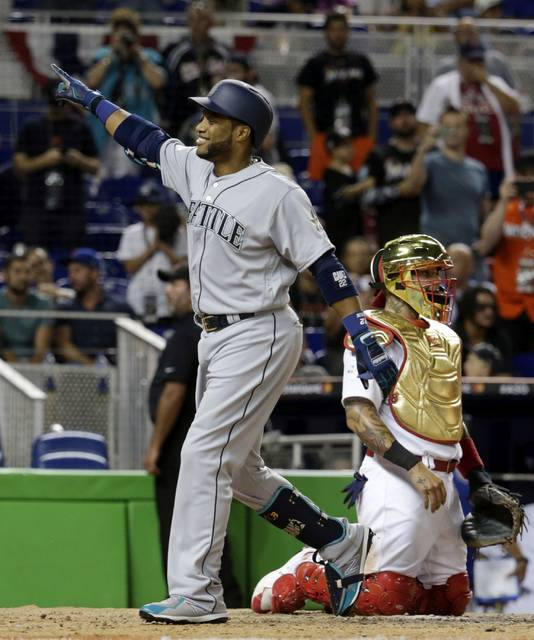 American League's Seattle Mariners Robinson Cano (22), points to his team after hitting a home run in the tenth inning, during the MLB baseball All-Star Game, Tuesday, July 11, 2017, in Miami. The American League defeated the National League 2-1. (AP Photo/Lynne Sladky)