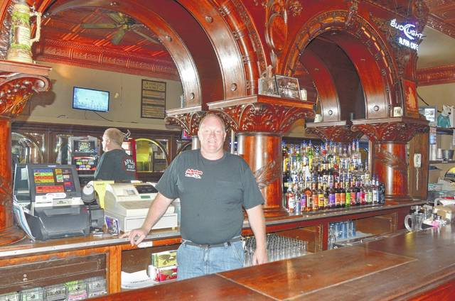 Alpha Cafe owner Tony Steinke stands near the 124-year-old bar that sits inside the establishment. The cafe opened in 1893 in downtown Wapakoneta.