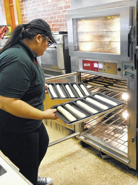 Denise Pierre-Bravo bakes some bread in the oven at Subway in Shawnee Township.