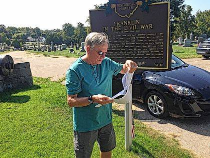 Dan Darragh, a history buff and longtime journalist in Franklin, Ohio, reviews histories of the city's contributions to the Union Army on Thursday, Aug. 24, 2017, near a cemetery's Civil War historical marker in Franklin, Ohio. Confederate Gen. Robert E. Lee never fought a Civil War battle in Ohio, but a 90-year-old roadside marker honoring Lee is sparking heated conflict in the city of Franklin, which sent Union troops to fight Lee, amid a national movement to remove Confederate monuments and flags from public land. (AP Photo/Dan Sewell)