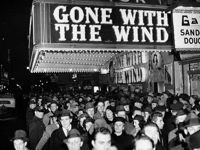 """FILE - In this Dec. 19, 1939 file photo, a crowd walks past the Astor Theater during the Broadway premiere of """"Gone With the Wind"""" in New York. A Memphis, Tennessee, theater has cancelled an annual screening of the classic 1939 film because of racially insensitive content. (AP Photo, File)"""