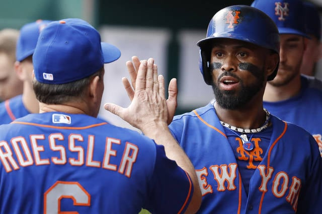 New York Mets' Jose Reyes, right, celebrates in the dugout after scoring on an RBI double by Wilmer Flores off Cincinnati Reds starting pitcher Homer Bailey in the first inning of a baseball game, Wednesday, Aug. 30, 2017, in Cincinnati. (AP Photo/John Minchillo)