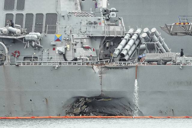 In this Tuesday file photo, the damaged port aft hull of the USS John S. McCain is visible while docked at Singapore's Changi naval base in Singapore. The wrenching deaths of sailors, drowned while trapped in their bunks on the USS John S. McCain has reverberated around the American fleet.