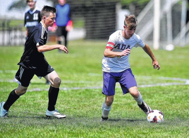 Ada's Logan Williams is defended by Spencerville's Grant Hackworth during Saturday's match in Ada.
