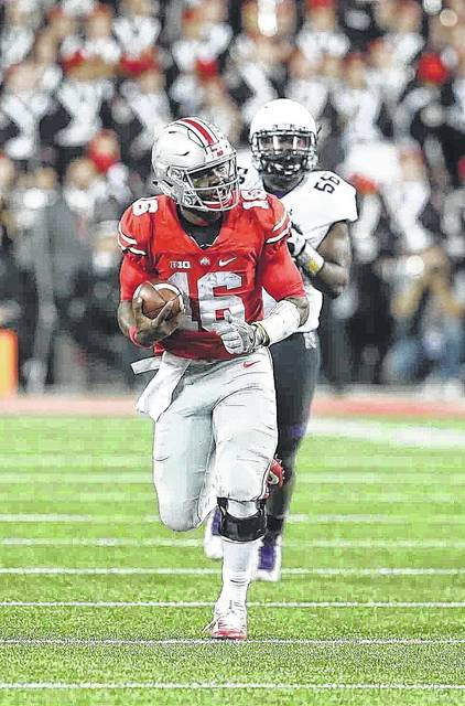 Ohio State #16 J.T. Barrett heads up field for a 35 yard  gain on a third and 10 late in the fourth quarter to seal the victory for Ohio State at Ohio Stadium on the campus of The Ohio State University October 29, 2016 Photo By Don Speck