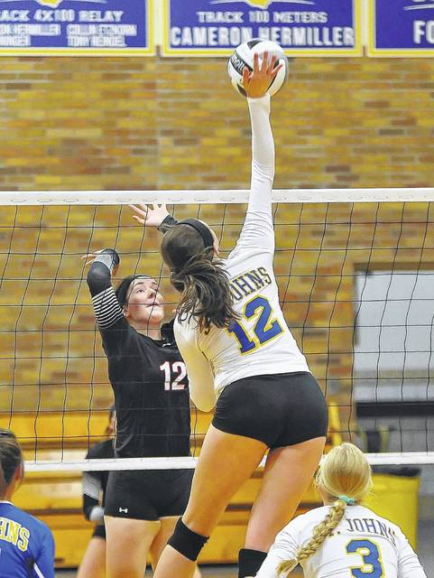 Madi Ellis of Delphos St. John's hits a spike against Spencerville's Abby Satterfield during Tuesday night's match at Robert A. Arnzen Gymnasium in Delphos.