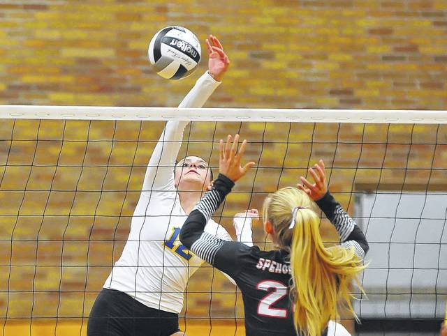 Madi Ellis of Delphos St. John's hits a spikes against Spencerville's Julie Mulholland during Tuesday night's match at Robert A. Arnzen Gymnasium in Delphos.