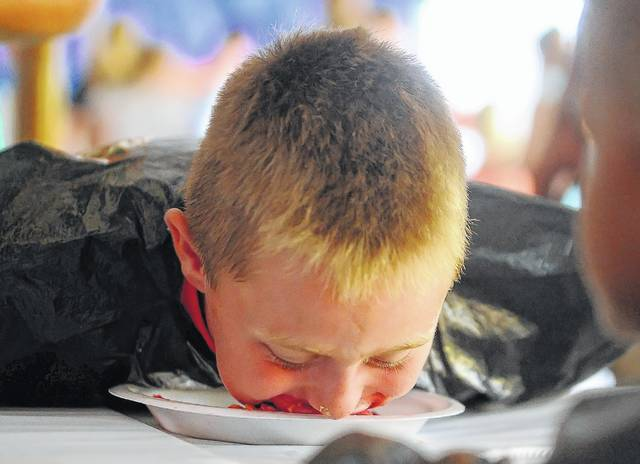 Peyton Bacome, 7, competes in the pie-eating contest during Monday's Allen County Fair at the Allen County Fairgrounds.