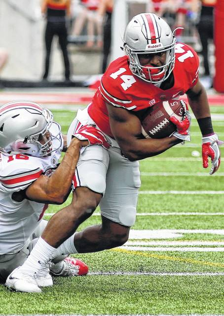 "FILE - In this April 15, 2017, file photo, Ohio State wide receiver K.J. Hill, right, is tackled by linebacker Keandre Jones during their NCAA college spring football game  in Columbus, Ohio. Six receivers are listed as ""starters"" on Ohio State's official depth chart released Monday, Aug. 28, 2017, a sure indication that all will get plenty of chances to shine in the season opener this week. (AP Photo/Jay LaPrete, File)"
