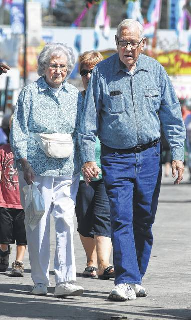 Eloise Hadsell, 89, and Ray Dunlap, 89, walk hand in hand down the midway while on a date during Senior Citizens Day at the Allen County Fair on Thursday. Hadsell is from Country Club Hills and Dunlap is from Lafayette.
