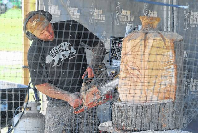 Joe Stebbing produces a wood carving with a chain saw during Wednesday's Allen County Fair at the Allen Country Fairgrounds.