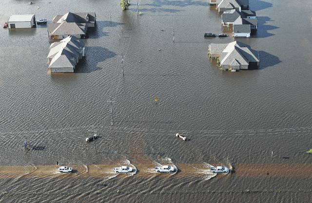 Cars drive through flooded streets from Tropical Storm Harvey in Orange, Texas, Thursday, Aug. 31, 2017. See page 5A for more coverage.