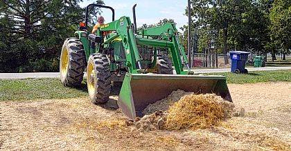 Jimmy Morrison uses a bulldozer to remove excess straw from a patch of dirt that served as a petting zoo at the Allen County Fair. Morrison was one of several people who helped with the clean-up process Sunday at the fairgrounds.