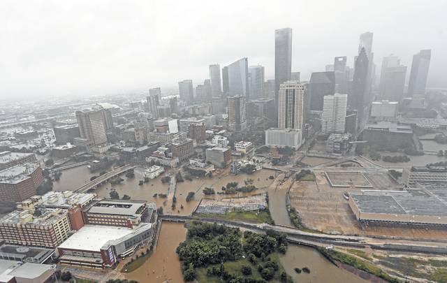 FILE - In this Tuesday, Aug. 29, 2017, file photo, highways around downtown Houston are empty as floodwaters from Harvey overflow from the bayous around the city in Houston. The Houston that was battered by Harvey is an economic powerhouse whose influence reaches far beyond its region, leading many to worry about when its economy be able to stand up again.