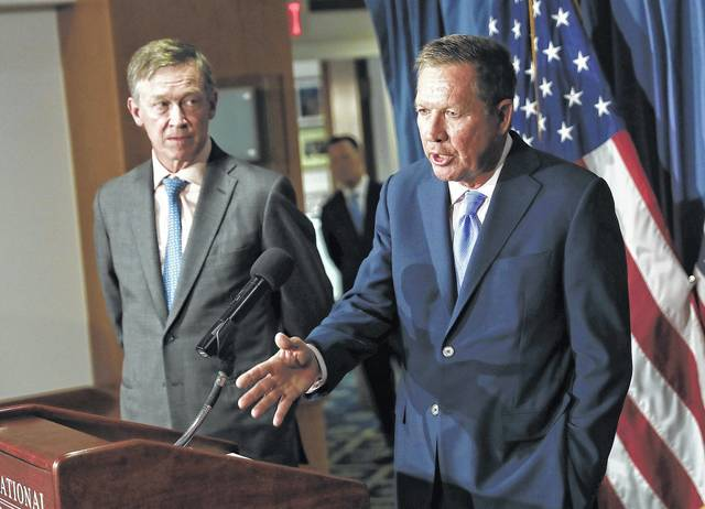 FILE - In this June 27, 2017, file photo, Ohio Gov. John Kasich, right, joined by Colorado Gov. John Hickenlooper, speaks during a news conference at the National Press Club in Washington. The bipartisan governor duo is urging Congress to retain the federal health care law's unpopular individual mandate while seeking to stabilize individual insurance markets as legislators continue work on a long-term replacement law. Kasich, and Hickenlooper shared their plan in a letter to congressional leaders Thursday, Aug. 31, 2017.