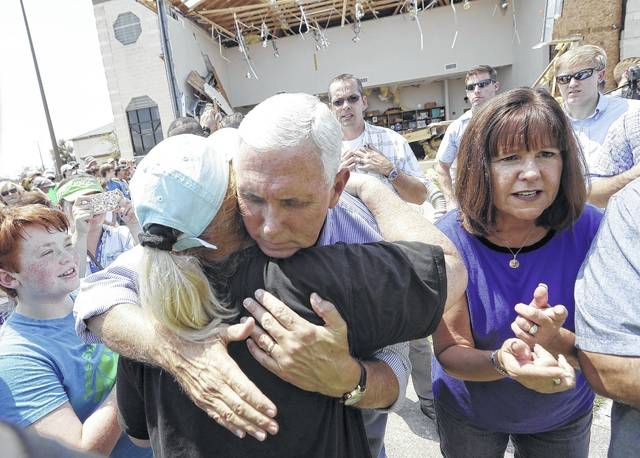 Vice President Mike Pence, center, with his wife Karen, right, shares a hug as he tries to encourage residents affected by Hurricane Harvey during a visit, Thursday, Aug. 31, 2017, in Rockport, Texas.