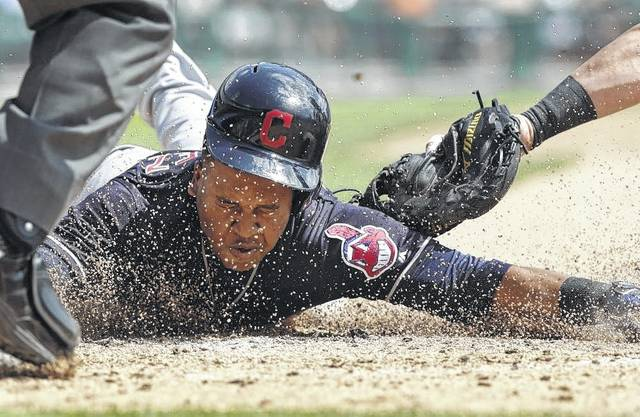 Cleveland's Jose Ramirez beats the tag of Tigers catcher James McCann to score a third-inning during Sunday's game in Detroit.