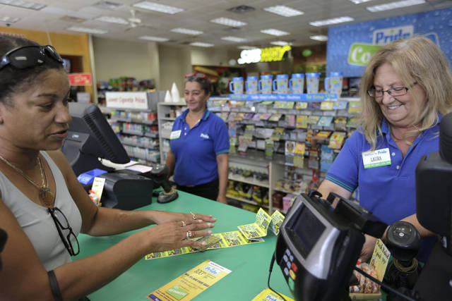 FILE- In this Aug. 24, 2017, file photo, Valerie Williams, of Springfield, Mass., left, buys lottery tickets at the Pride Station & Store, in Chicopee, Mass., where the lone winning ticket for the $758.7 million Powerball drawing was sold. The Massachusetts State Lottery has retired the machine that printed the winning ticket belonging to Mavis Wanczyk. The Powerball jackpot she claimed last week is the largest grand prize won by a lottery ticket in U.S. history. (AP Photo/Steven Senne, File)