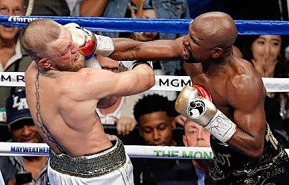 FILE - In this Aug. 26, 2017, file photo, Floyd Mayweather Jr. hits Conor McGregor in a super welterweight boxing match in Las Vegas. The AP reported on Sept. 1, 2017, that a story claiming a boxing promoter connected to the fight was found shot dead in Washington, D.C. is a hoax. (AP Photo/Eric Jamison, File)