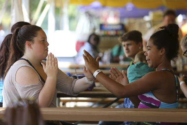 Lillian Bruner, 15, left, and Tianna Pearson, 11, play Patty Cake during the 2017 Cincinnati AFL-CIO Labor Day Picnic, Monday, Sept. 4, 2017, at Coney Island in Cincinatti.  (Kareem Elgazzar/The Cincinnati Enquirer via AP)