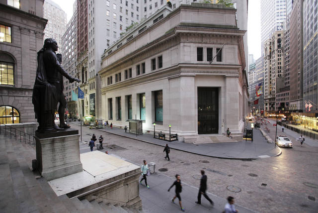 FILE - In this Oct. 8, 2014, file photo, people walk to work on Wall Street beneath a statue of George Washington, in New York.  Global stock markets edged up on Monday, Sept. 18, 2017, as investors looked ahead to a U.S. Federal Reserve meeting and U.S. President Donald Trump's speech at the United Nations. (AP Photo/Mark Lennihan, File)