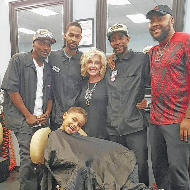Leslie Schuh, owner of Ahmee Elite Design, poses with Fresh N Faded employees Gregory Cunningham, far left, James Henderson, Alvin Conley and James Allison, as well as a young patron, Antonio Weis. The hair studios are offering free haircuts to needy students at Elida schools, but they hope to expand to other districts in the future.
