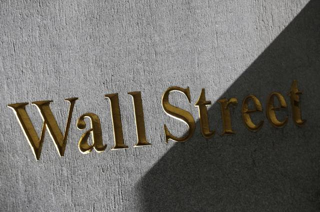 FILE - This March 4, 2013, file photo shows a sign for Wall Street on the side of building near the New York Stock Exchange. Stocks are opening slightly higher on Wall Street, Tuesday, Oct. 10, 2017, led by gains in technology and consumer products makers. (AP Photo/Mark Lennihan, File)