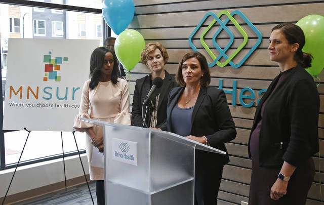 In this Oct. 26, 2017, photo, Allison O'Toole, second from right, speaks to the media at the new offices of Briva Health, MNsure's largest enrollment partner, in Minneapolis. Health care consumers in most of the country are encountering a world of confusion and chaos as the open enrollment period to sign up for coverage approaches. The outlook is decidedly different in the 12 states that operate their own marketplaces. California, Colorado, Minnesota and other states that operate autonomous exchanges are pulling out all the stops to inform consumers. Also shown, from left, Hodan Guled, chief executive officer of Briva Health, Minneapolis Major Betsy Hodges and at right, Emily Piper, commissioner of Minnesota Human Services. (AP Photo/Jim Mone)