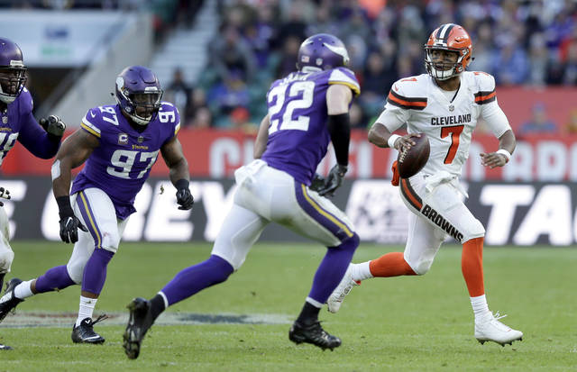 Cleveland Browns quarterback DeShone Kizer (7) scrambles away from Minnesota Vikings safety Harrison Smith (22) and defensive end Everson Griffen (97) during the second half of an NFL football game at Twickenham Stadium in London Sunday.