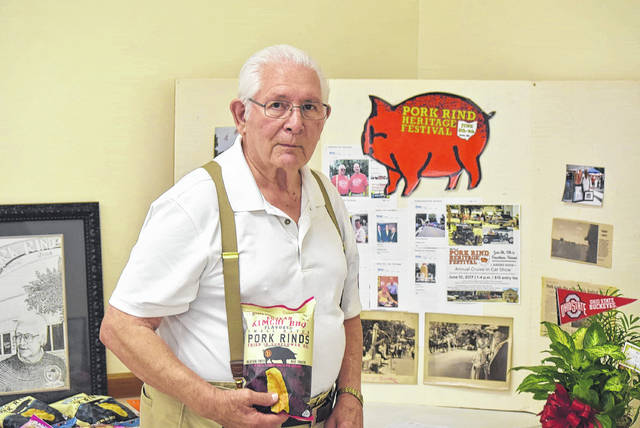 Former Harrod Mayor Bill Gossard holds a bag of pork rinds from Rudolph Foods