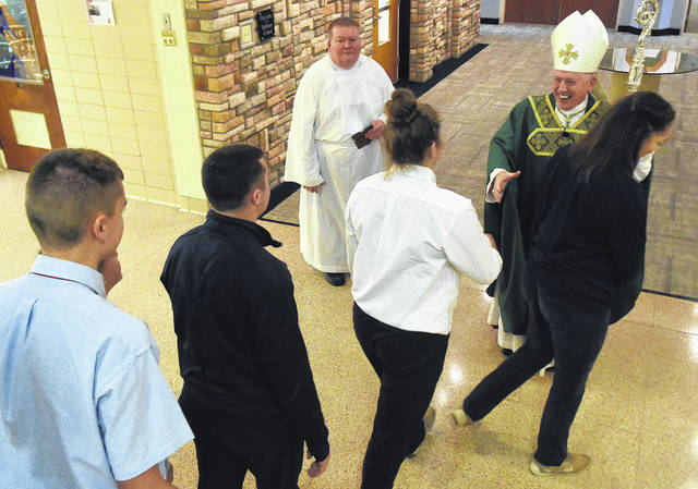 Thomas greets students at LCC Thursday. He is on a tour of high schools in the diocese to reach out to young people.